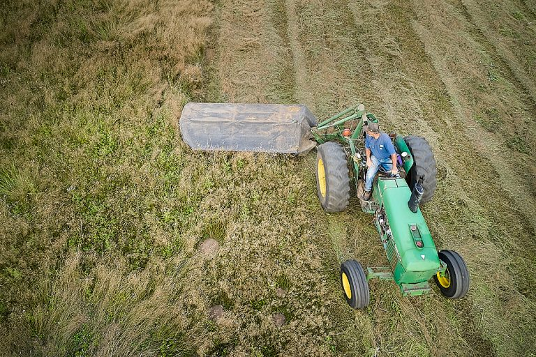 Drone photo of tractor cutting hay.